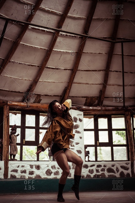 Mixed race fashionable dancer dances in stone  and straw dome studio