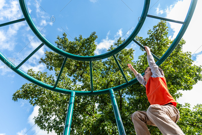 Young boy swinging from monkey bars during a nice summer day.