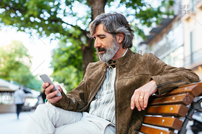 Mature man texting with a mobile phone while he is sitting on a street's bench.