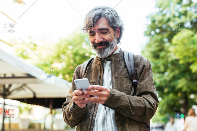 Mature man texting with a mobile phone in the street.