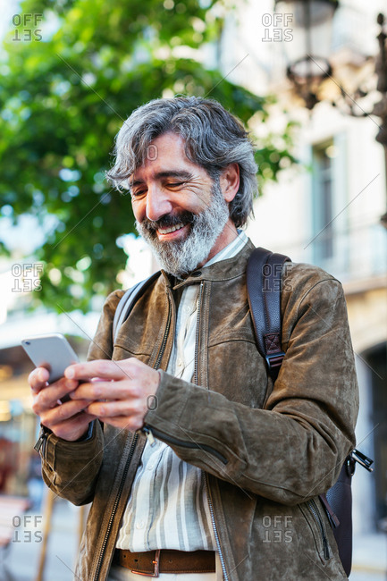 Mature man using a mobile phone in the street.