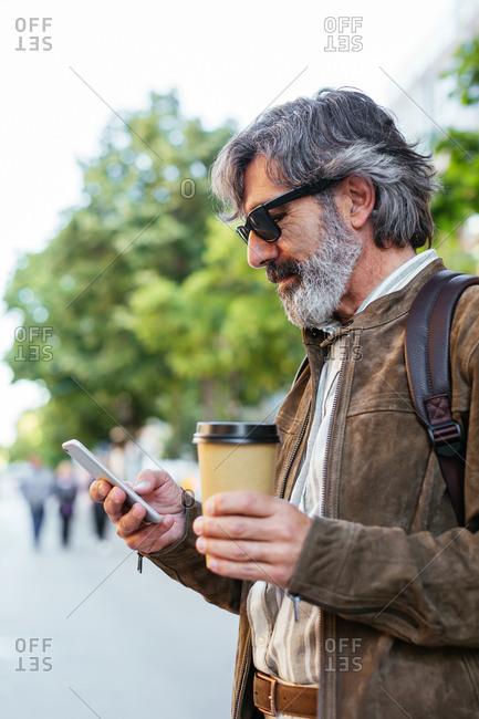 Mature man wearing glasses using a mobile phone in the street.