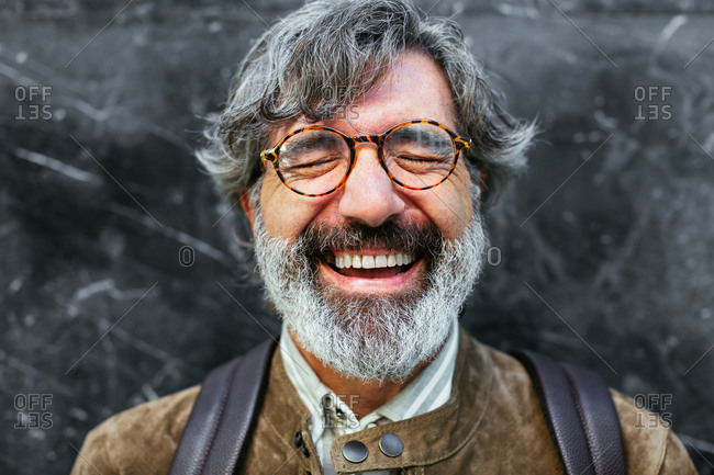 Happy mature man laughing in front of the camera.