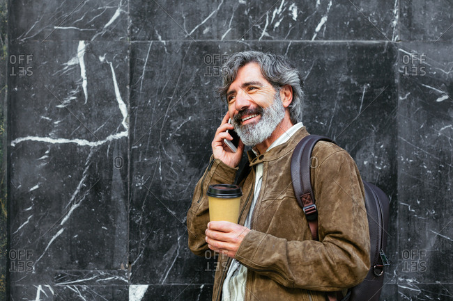 Happy mature man talking by mobile phone with a coffee in the street.