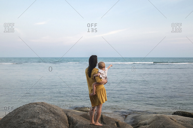 Woman and baby looking out over the ocean on Koh Samui, Thailand