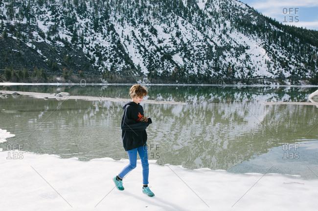 A teen girl holding a pinecone walks along a partially frozen lake