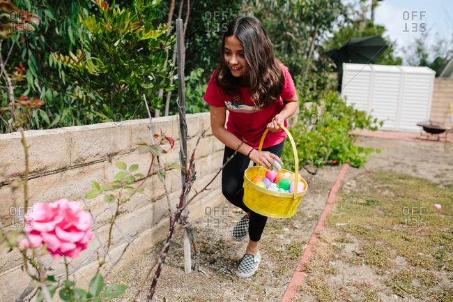 Girl smiles as she collects Easter eggs during an Easter egg hunt