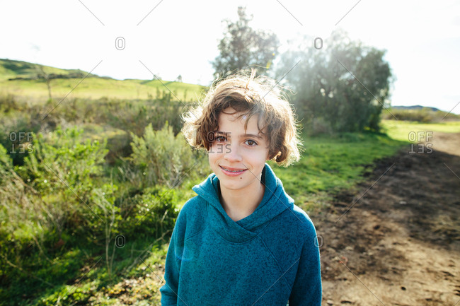 Girl with braces smiles while outside on a nature trail