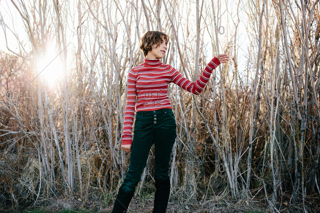 Teen girl with short hair and turtleneck stands in the woods