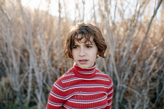 Teen girl with braces wearing a turtleneck stands outside by the woods
