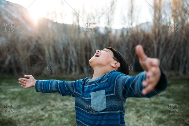 Boy outside with arms wide joyfully yells toward the sky