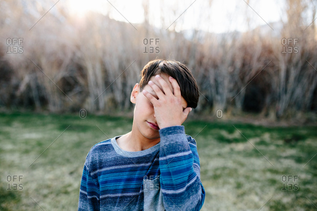 Boy outside appears sad as he covers part of his face with his hand
