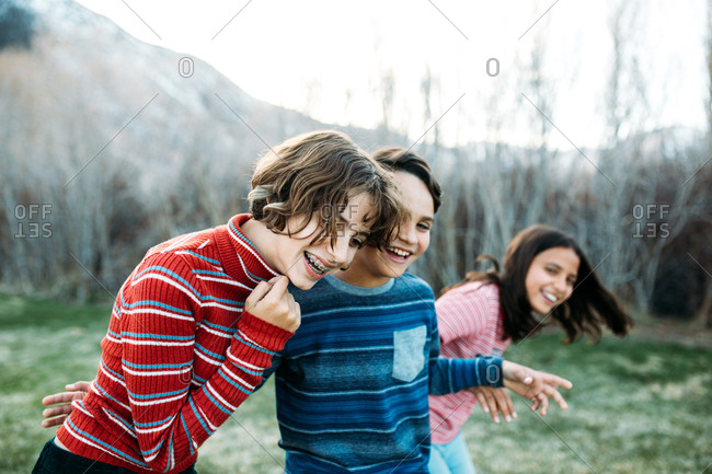 Brother with two sisters laughing together while outside