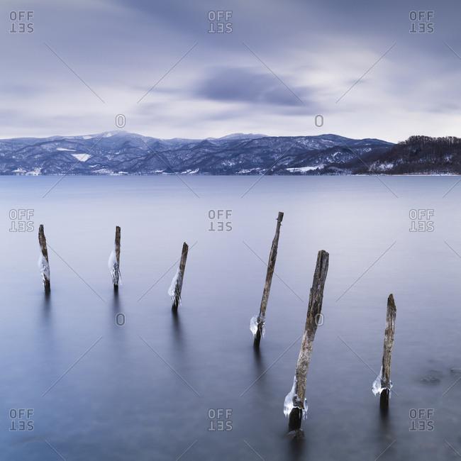 Long exposure shot of wooden sticks in the water at Lake Toya, Hokkaido, japan