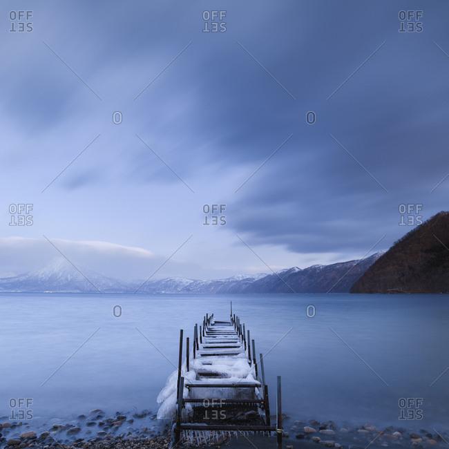 Long exposure shot of boat pier covered in ice at Lake Shikotsu, Hokkaido, japan