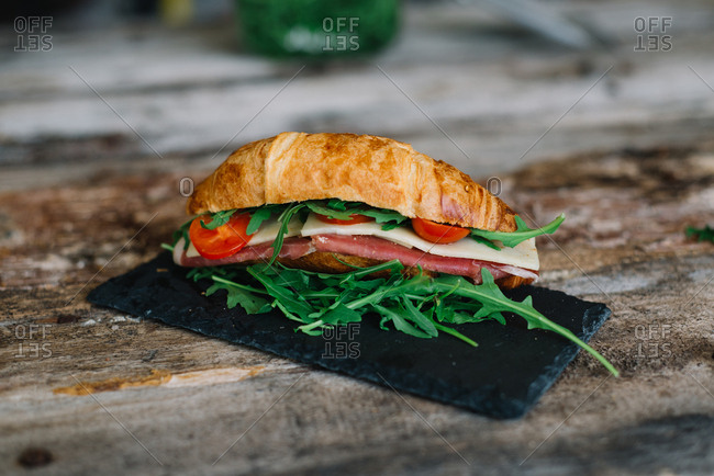Fresh croissant sandwich with salad, ham, cheese and tomatoes on table