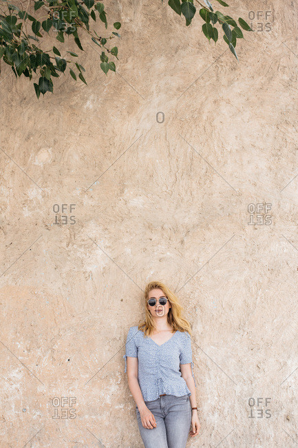 Young woman standing and leaning against the wall