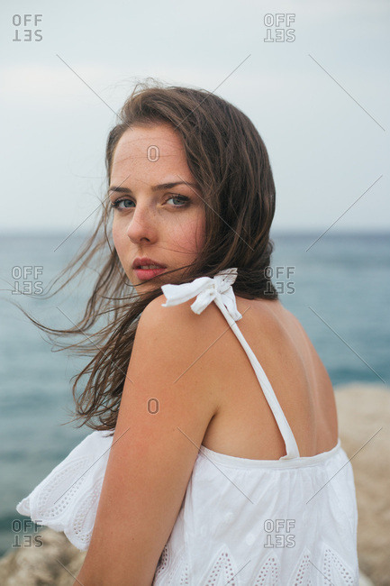 Close-up portrait of young woman in white summer dress