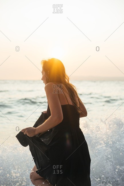 Young woman in black summer dress being splashed by sea waves