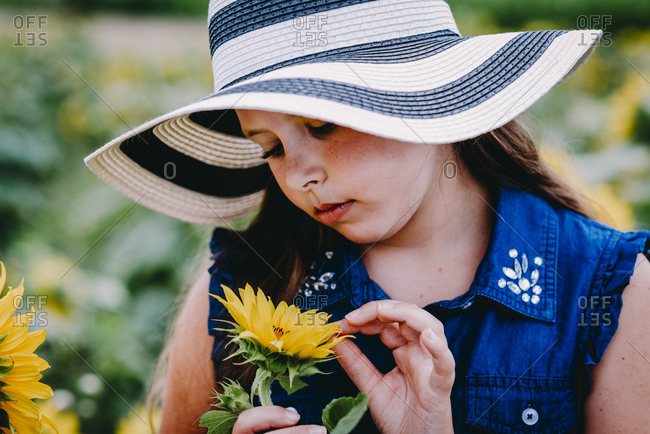 Girl wearing a straw hat looking at a sunflower