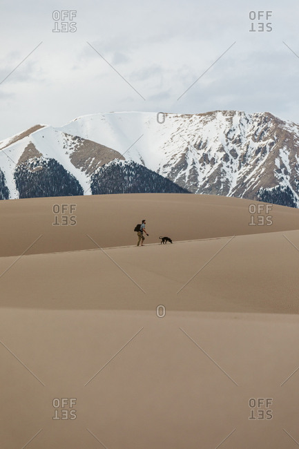 Male hiker with dog on leash hikes in the great sand dunes of Colorado