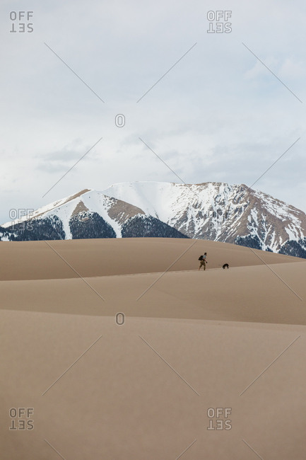 Male hiker with puppy hike the layered sand dunes under snowy mountain