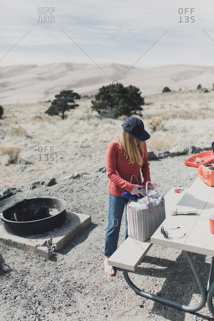 Woman at campsite packs a bag at picnic table with dunes in background