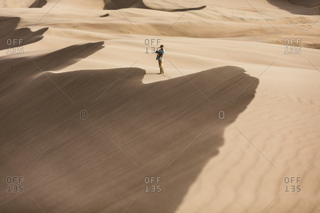 Man holds his dog in the windy sand dune ridges of great sand dunes