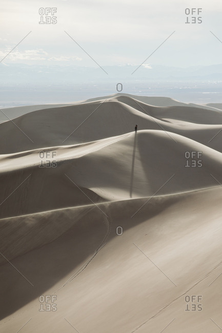 Hiker stands on top of a distant ridge at Great Sand Dunes Park