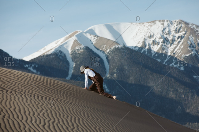 Tired wanderer climbs on hands and knees up sand dune