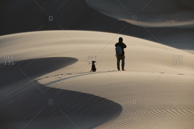 Man and his puppy explore the sand dune deserts of Colorado