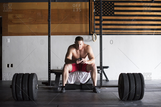 A weightlifter takes notes in his phone during a workout.
