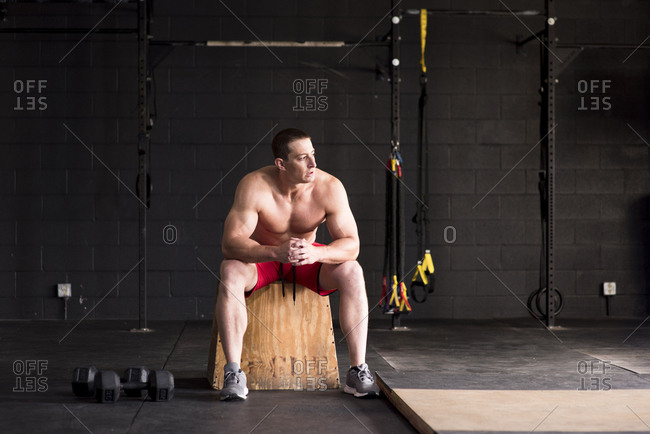 An athlete rests on a wood box during a workout at a gym.