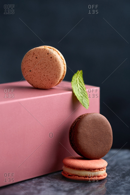 Macarons with pink box, green leaf and blue background
