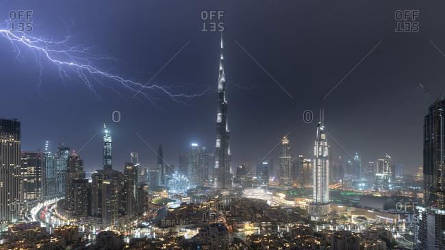 March 17, 2019: Dubai skyline and Burj Khalifa under stormy night sky with lightning