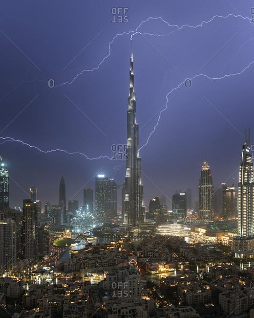 March 17, 2019: Night view of Dubai skyline with lightning striking Burj Khalifa