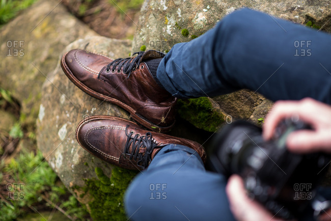 Man wearing leather boots sitting on rocks with camera