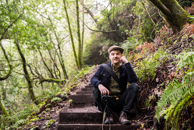 Man smiling at camera and sitting on wooden steps in forest