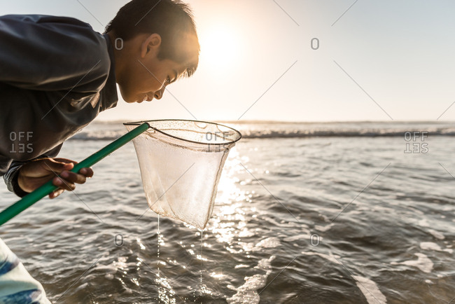 Happy young boy looking in a net illuminated by the sun at a beach