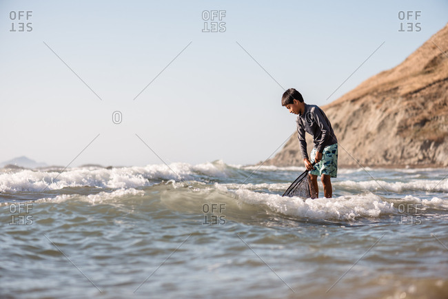 Pre-teen boy holding a net and looking in the water at a beach