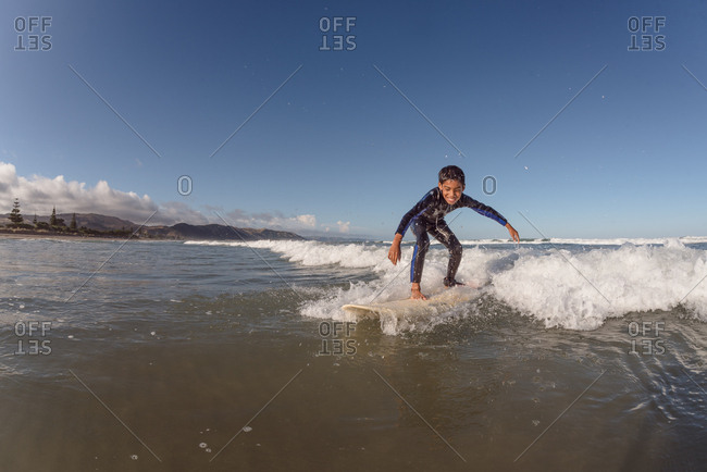 Happy pre-teen boy surfing on a wave under a blue sky
