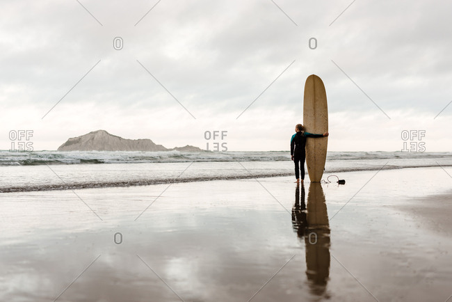 Pre-teen girl standing on a beach next to a surfboard