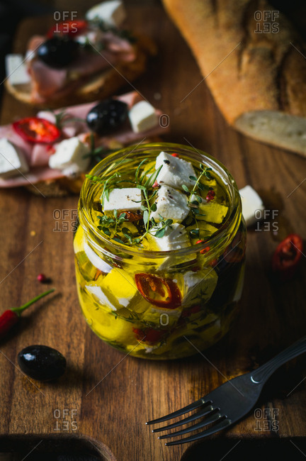 Marinated goat cheese with fresh herbs, spices and chili peppers in olive oil