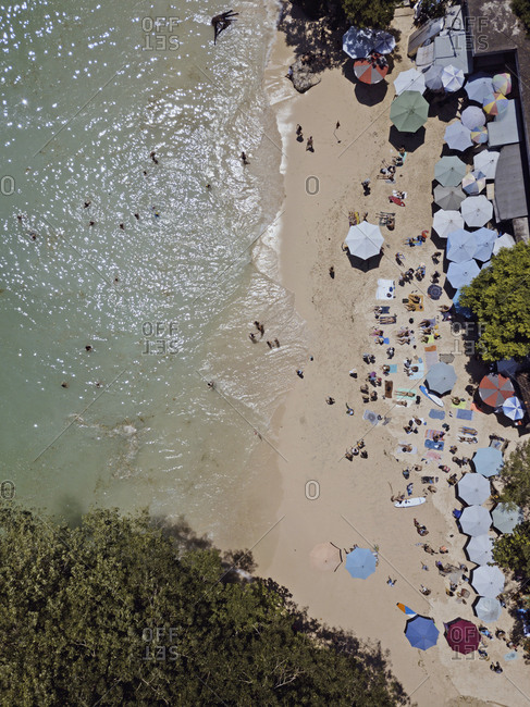 Bali, Indonesia - August, 25, 2019: Overhead view of beachgoers at Padang Padang beach