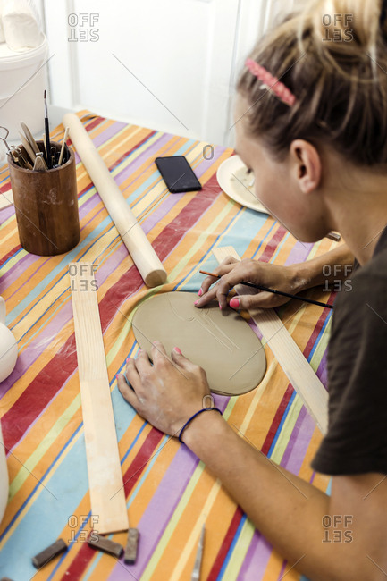 Woman decorating a plate in a ceramics workshop