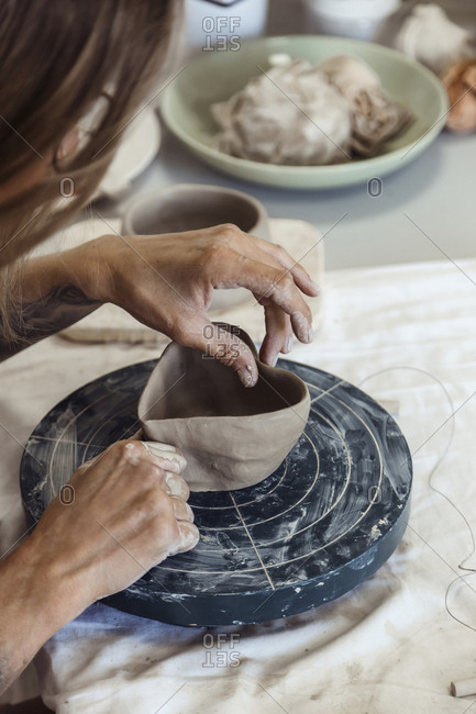 Female potter making a heart shaped pot with clay in workshop