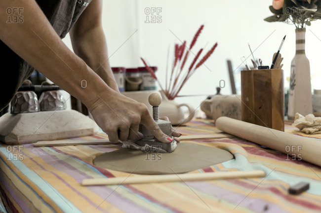 Hand's of a woman working with clay in a ceramics workshop