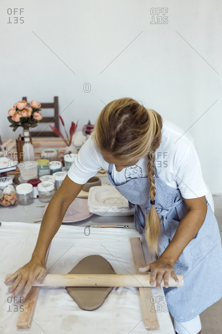 Woman rolling clay with rolling pin in studio