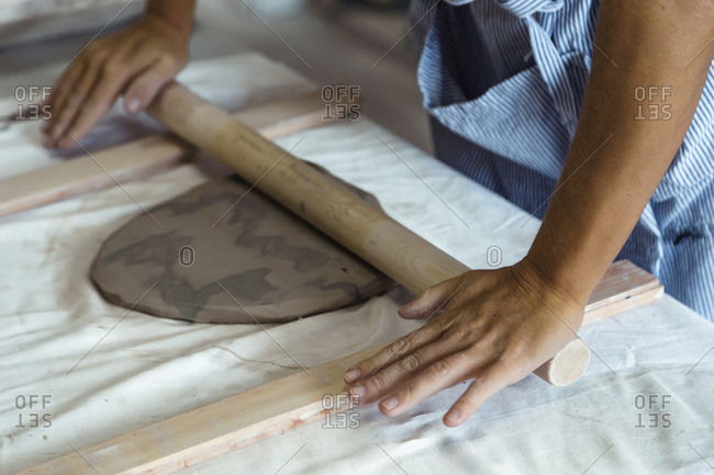 Close up of woman rolling clay with rolling pin in studio