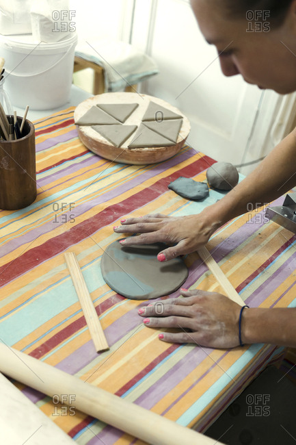 A woman decorating a plate in a ceramics workshop